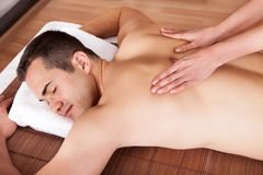 Young man getting shoulder massage Royalty Free Stock Photo