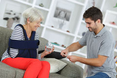 Young man getting tablets for lady with arm in sling Stock Photos