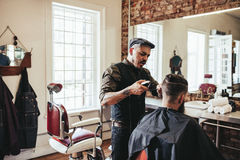 Young man getting trendy haircut at barbershop stock photo