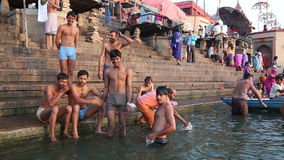 Young man at ghats of the Ganges in Varanasi, with people bathing around them. VARANASI, INDIA - 22 FEBRUARY 2015: Young man at ghats of the Ganges in Varanasi stock video