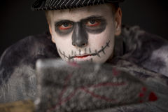 Young man in ghoulish Halloween makeup. Young man in ghoulish Halloween skull makeup wrapped in dark clothing and hat brandishing a bloodied knife at the camera stock photography