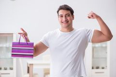 The young man with gift bag at home preparing suprise for wife. Young man with gift bag at home preparing suprise for wife Royalty Free Stock Photos