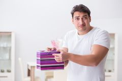 The young man with gift bag at home preparing suprise for wife. Young man with gift bag at home preparing suprise for wife Royalty Free Stock Image