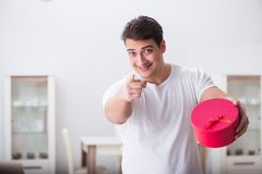 The young man with gift bag at home preparing suprise for wife. Young man with gift bag at home preparing suprise for wife Royalty Free Stock Images