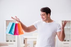 The young man with gift bag at home preparing suprise for wife. Young man with gift bag at home preparing suprise for wife Royalty Free Stock Photo