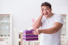The young man with gift bag at home preparing suprise for wife. Young man with gift bag at home preparing suprise for wife Royalty Free Stock Photography