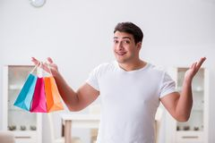 The young man with gift bag at home preparing suprise for wife. Young man with gift bag at home preparing suprise for wife Stock Image