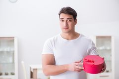 The young man with gift bag at home preparing suprise for wife. Young man with gift bag at home preparing suprise for wife Stock Photo