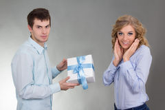 Young man with gift and surprised girlfriend Royalty Free Stock Image