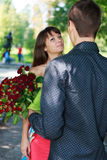 Young man gift a woman a bouquet of red roses in a summer park. Sunny outdoor Stock Photos