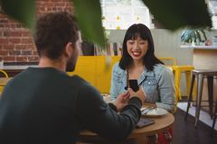 Young man gifting ring to girlfriend in cafe Stock Photography