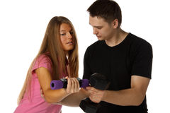 Young man and the girl with dumbbells Royalty Free Stock Photography