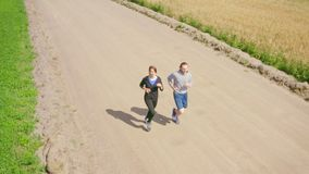 A young man and a girl jog along a dirt road next to green and cereal fields.