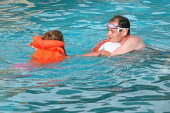 Young man and girl in lifejacket bathing in pool. Young man and little girl in lifejacket bathing  in pool on resort Royalty Free Stock Photos