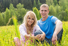 Young man and girl on meadow Royalty Free Stock Photo