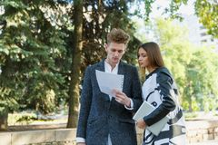 Young man and girl outdoors looking at documents. stock photos