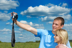 Young man and girl are photographed. Young man and woman do a self-portrait against a green field and the dark blue sky with clouds Stock Image