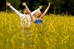 Young man and girl on rye field. Young pair laugh and lift hands against the field which have grown with a rye Stock Images