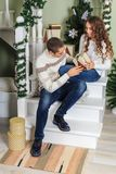 Young man and a young girl are sitting on the steps of a white staircase in a house in the eve of New Year holidays. The guy looki. Young men and a young girl stock images