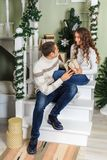 Young man and a young girl are sitting on the steps of a white staircase in a house in the eve of New Year holidays. The guy looki. Young men and a young girl royalty free stock images