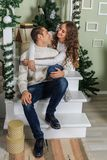 Young man and a young girl are sitting on the steps of a white staircase in a house in the eve of New Year holidays. Girl and guy. Young men and a young girl are royalty free stock photos