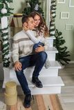 Young man and a young girl are sitting on the steps of a white staircase in a house in the eve of New Year holidays. Girl is huggi. Young men and a young girl royalty free stock photography