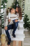 Young man and a young girl are sitting on the steps of a white staircase in a house in the eve of New Year holidays. Girl is huggi. Young men and a young girl royalty free stock image
