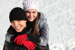 Young man and girl smiling and looking at camera. Portrait of young man and girl smiling and looking at camera, girl embracing man from back, winter day Stock Images