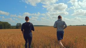 A young man and a girl with sports figures in sportswear are running along a cereal field. Summer day. In the background a blue sky with clouds and a forest stock footage