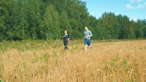 A young man and a girl with sports figures in sportswear are running along a cereal field. Summer day. In the background a blue sky with clouds and a forest stock video