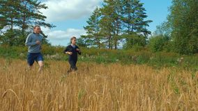 A young man and a girl with sports figures in sportswear are running along a cereal field. Summer day. In the background a blue sky with clouds and a forest stock video footage