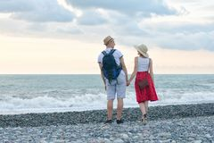 Young man and girl are standing on the beach and looking at each other against the background of the sea and sky. Young men and girl are standing on the beach Royalty Free Stock Images