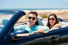 Young man with girlfriend in cabriolet. Royalty Free Stock Photos