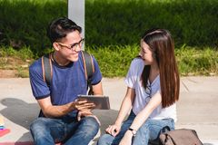 Young Man and girls friend classmates sitting consult. On laptop at university together royalty free stock photography