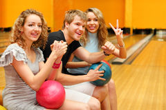 Young man and girls sit with balls in bowling club Stock Photos