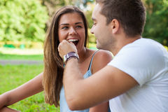 Young man gives cherry to his girlfriend. He feeds her Royalty Free Stock Photos