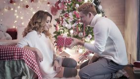 A young man gives a Christmas present to a beautiful young woman sitting near a Christmas tree. They smile together. A young man gives a Christmas present to a stock video footage