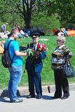 Young man gives flowers to a veteran Royalty Free Stock Image