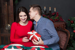Young man gives a gift to beautiful woman Stock Images