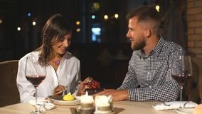 The young man gives a gift to a young girl in the cafe stock footage