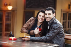 The young man gives a gift to a young girl in the cafe and they Royalty Free Stock Photography