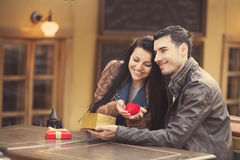 The young man gives a gift to a young girl in the cafe and they royalty free stock photos