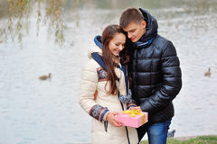 The young man gives a gift to a young girl in the cafe and they Stock Photos