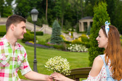 Young man gives a girl flowers on footbridge in park Royalty Free Stock Images