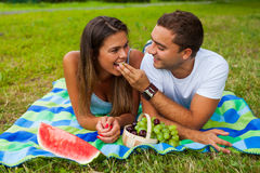 Young man gives grape to his girlfriend. He feeds her Stock Photos