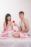 Young man gives heart beautiful girl in bed Royalty Free Stock Photo