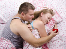 A young man gives a ring girl lying in bed Stock Photos