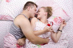 A young man gives a ring girl lying in bed Stock Photo
