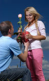 The young man gives a rose and heart to girl. The young man gives a pink flower and plush heart to  beautiful gentle girl Royalty Free Stock Photos