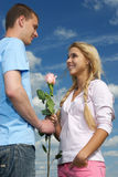The young man gives a rose to girl. The young man gives a pink flower to  beautiful gentle girl Stock Photo